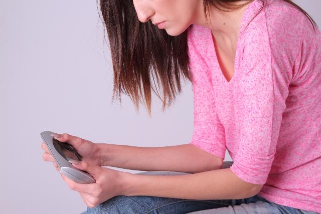 携帯ゲームをする女性